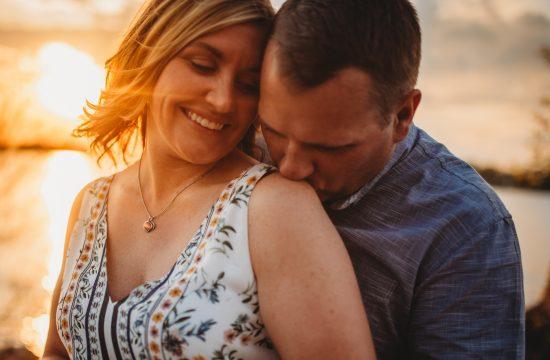 man kissing woman's shoulder in sunset on lake minnetonka