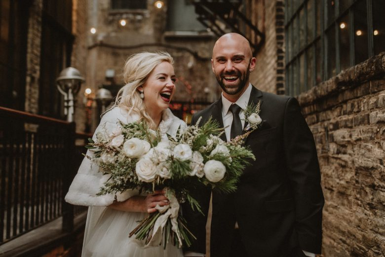 Bride holding large bouquet and laughing with her groom