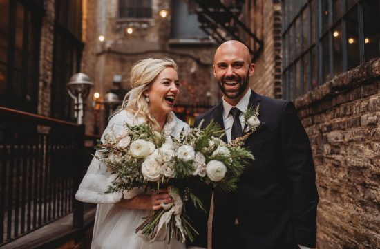 Bride and groom standing in alleyway laughing