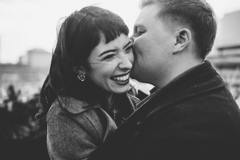Lesbian couple laughing and dancing in black and white