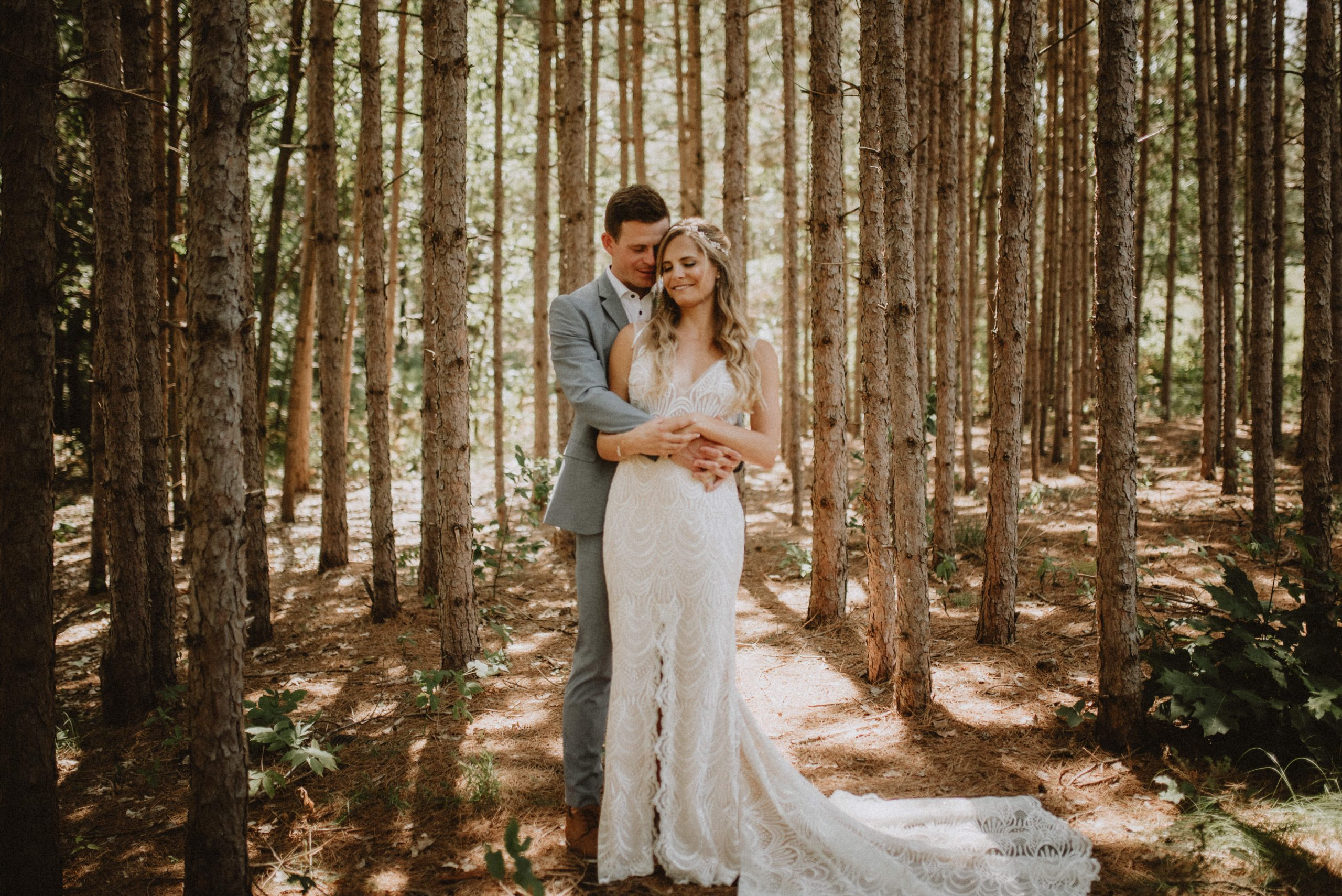 Groom holding bride from behind in tall pine forest