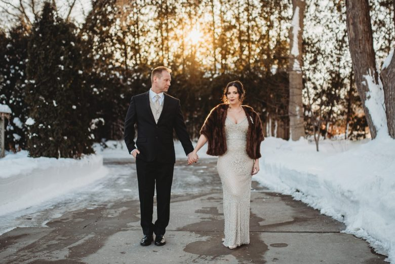 Vintage bride and groom holding hands outside at winter wedding