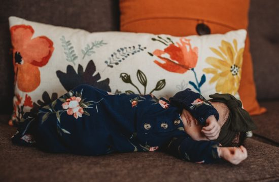 Baby in floral onesie sleeping on couch