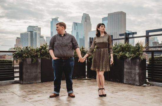 Two women standing and holding hands on Hewing Hotel rooftop with Minneapolis skyline behind them