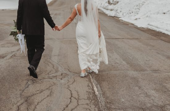 Bride and groom holding hands and walking down a winter road