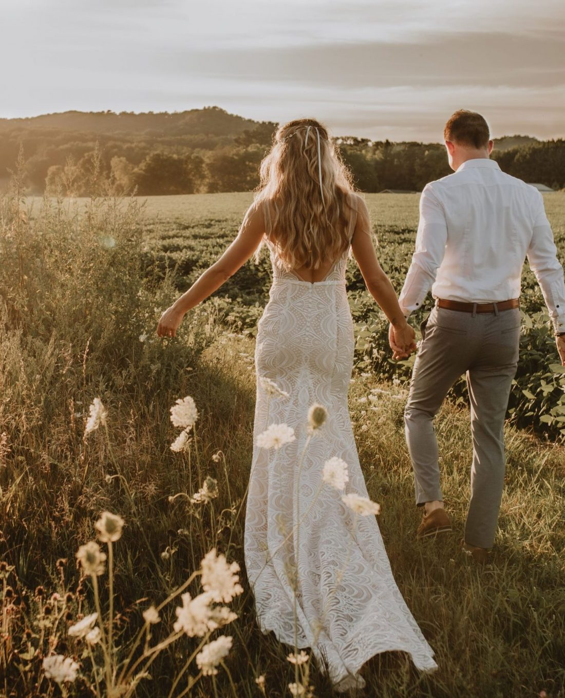 Bride and groom frolicking through a sunset flower field