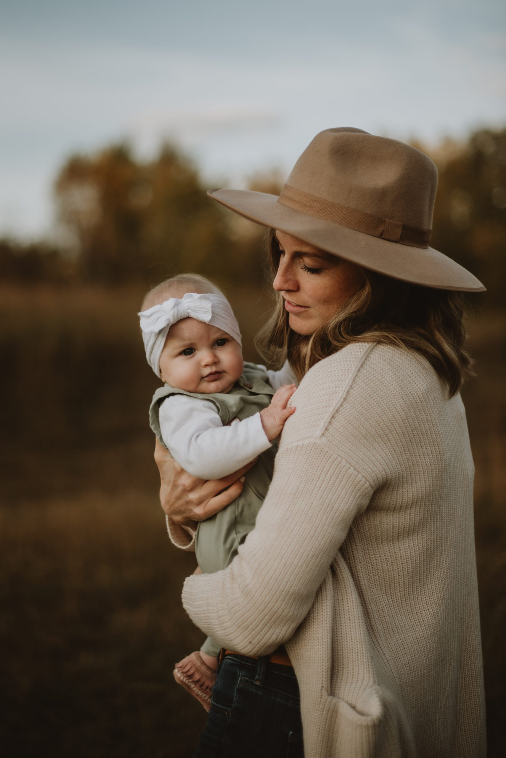Woman in hat holding baby daughter in a field