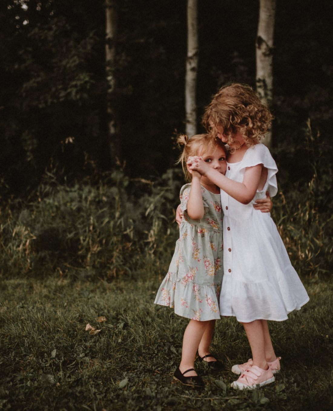 little sisters dancing together in the forest