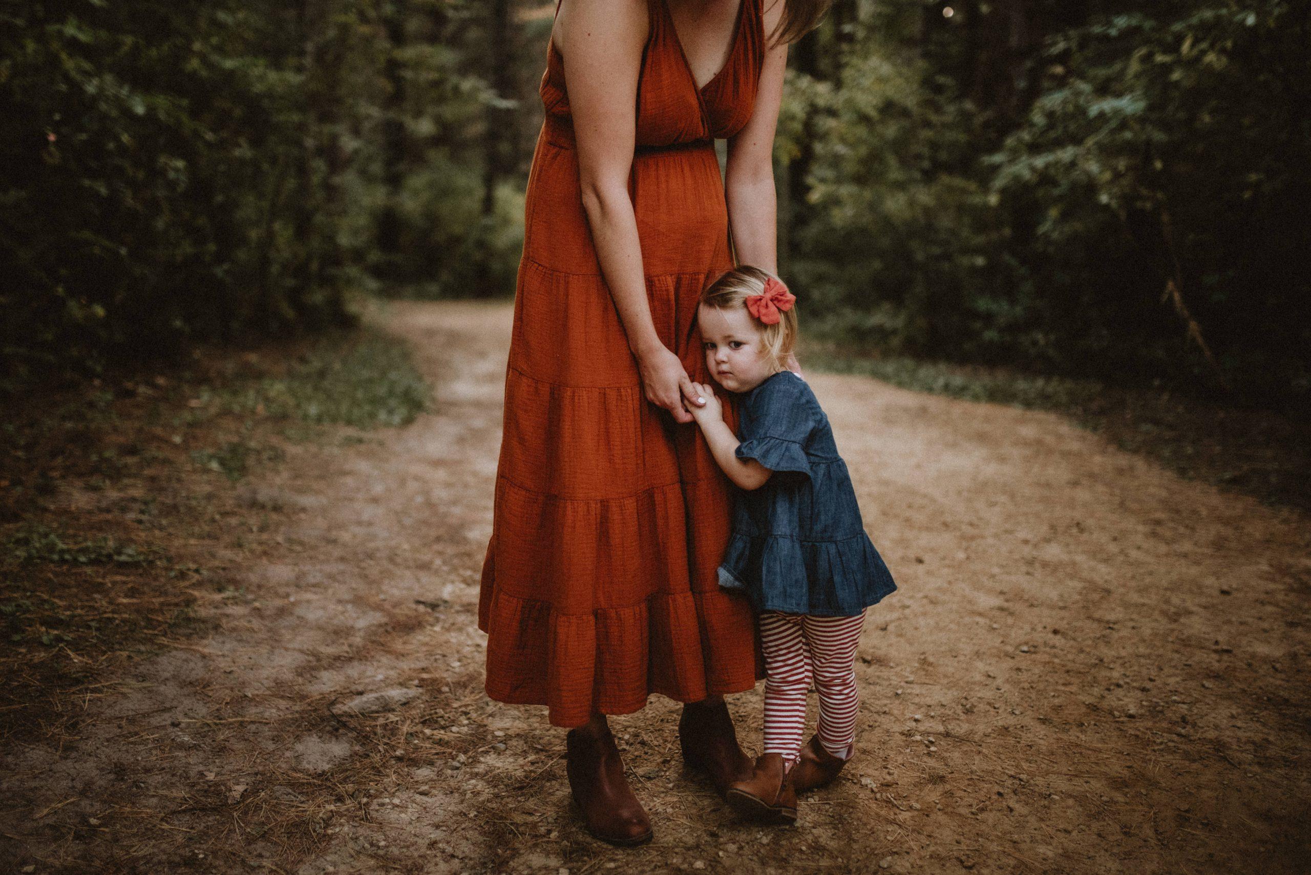 Little girl hugging her mom's legs in forest