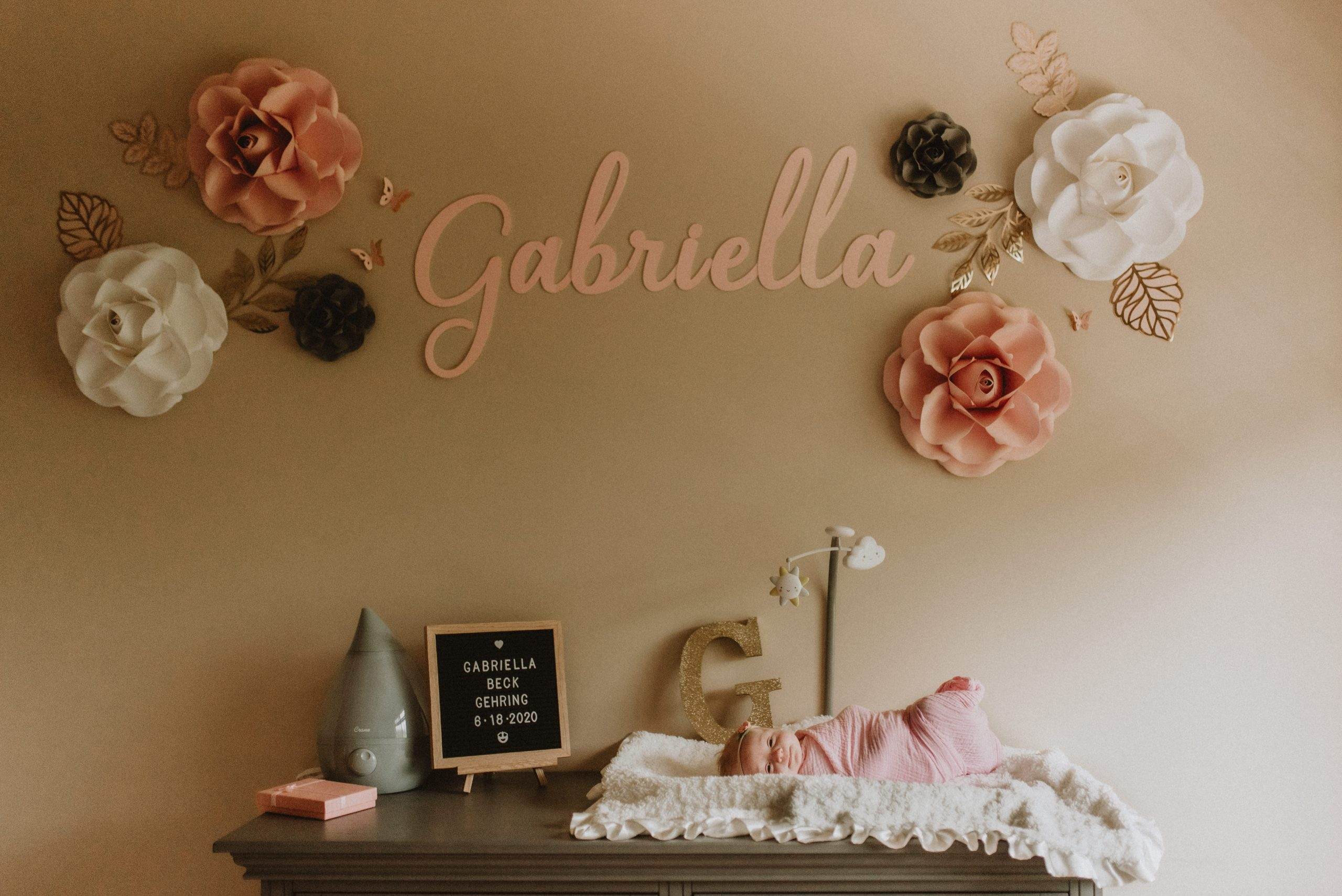 Newborn baby swaddled on her changing table in her nursery