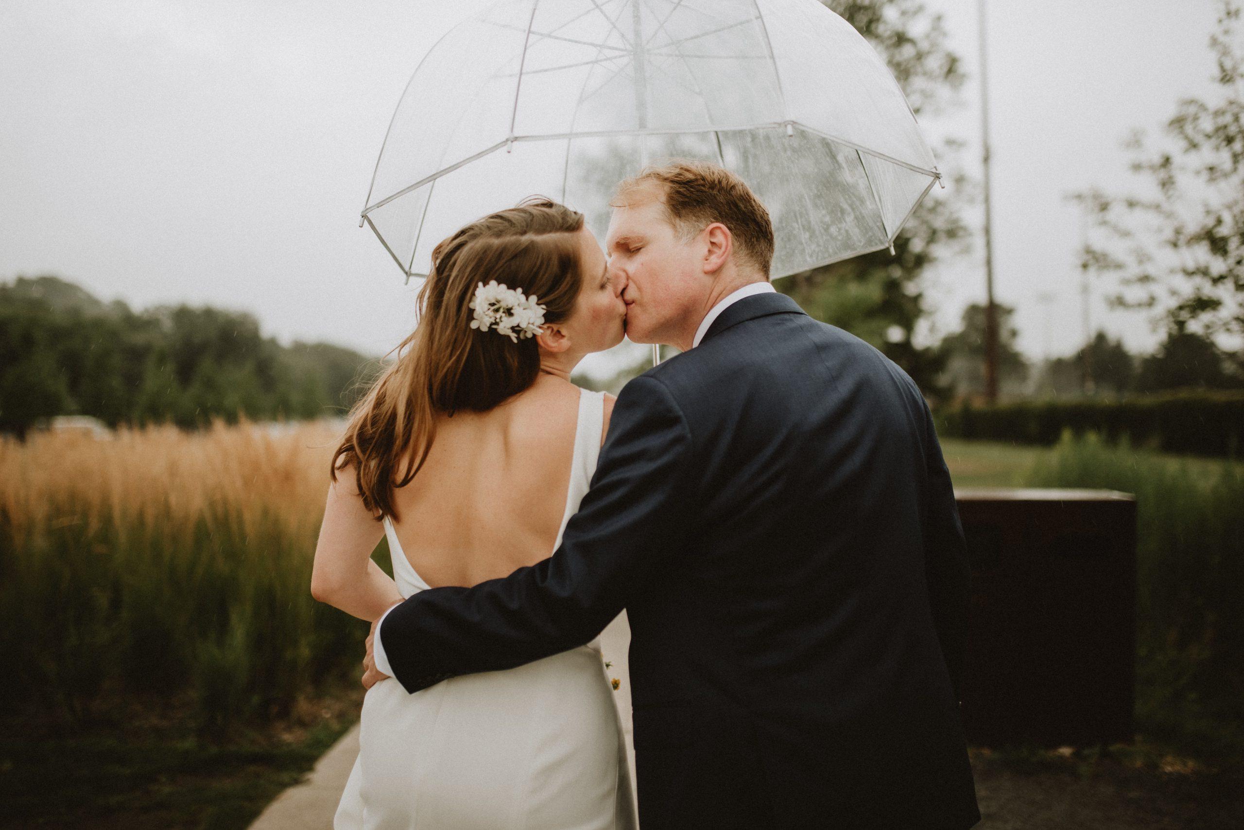 Bride and groom kiss under umbrella in the rain