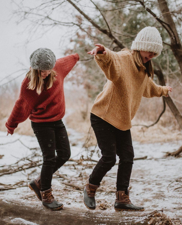 Twin 10 year old girls walking on a fallen log