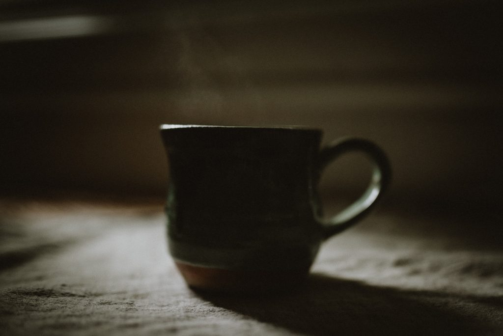 Dark silhouette of a mug with steam coming out the top
